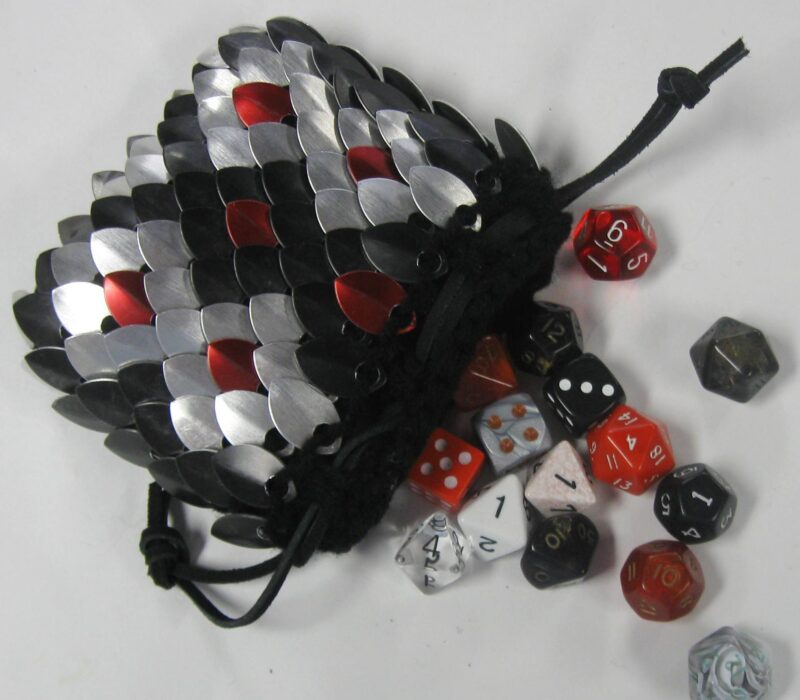 A snakeskin-patterned scalemaille dicebag in black, silver, and red; spilling dice out on the table.