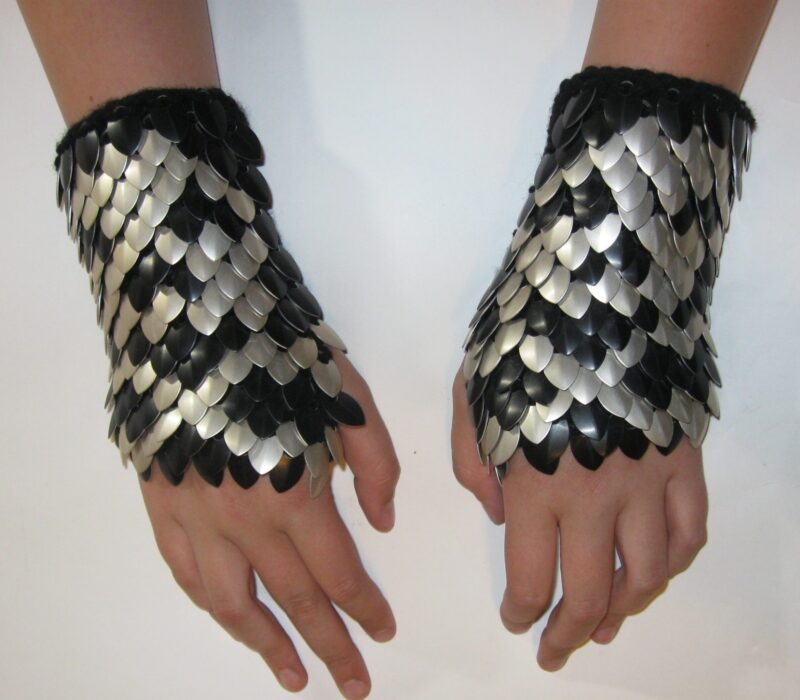 A pair of black knitted scalemaille gauntlets with silver skull and crossbones patterns