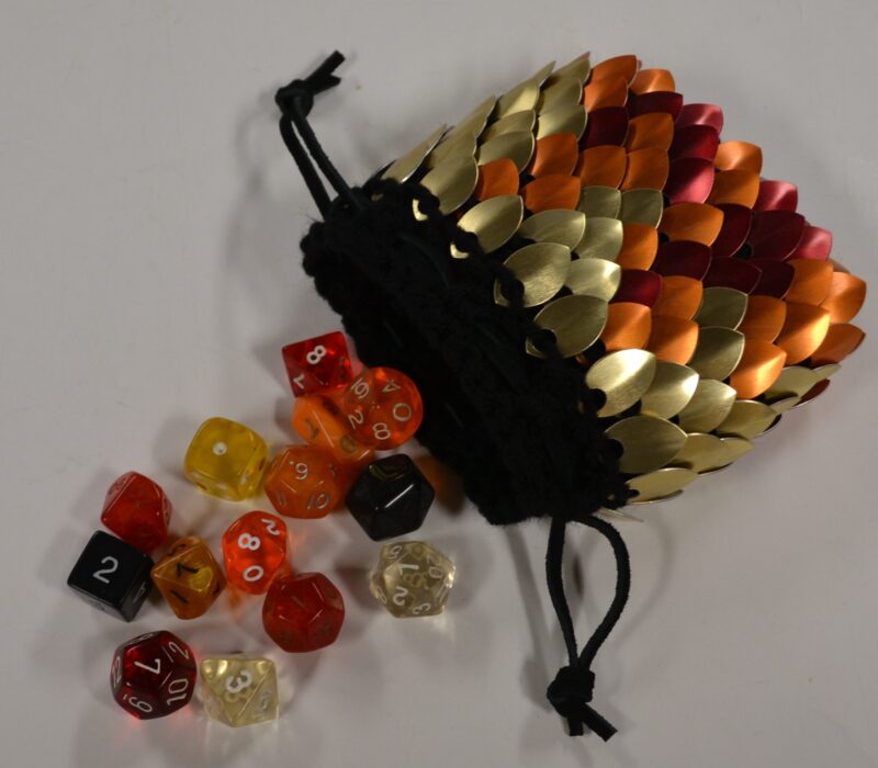 A medium, fire-patterned scalemaille dicebag on black yarn, spilling dice on the table.