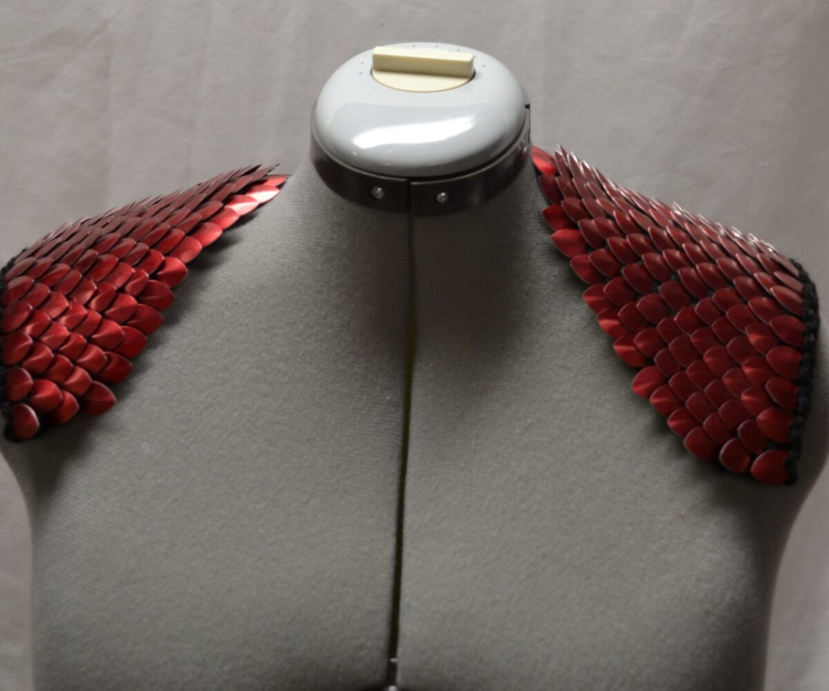 Red scailemaille epaulets, scales pointing in towards the neck, modelled on a dress form.