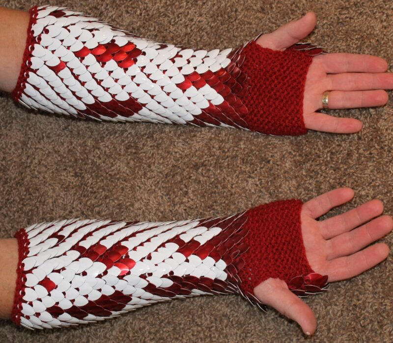 The palm side of a pair of long white and red dragonhide gauntlets, showing the red yarn lining and the scalemaille wrapping around the arms.