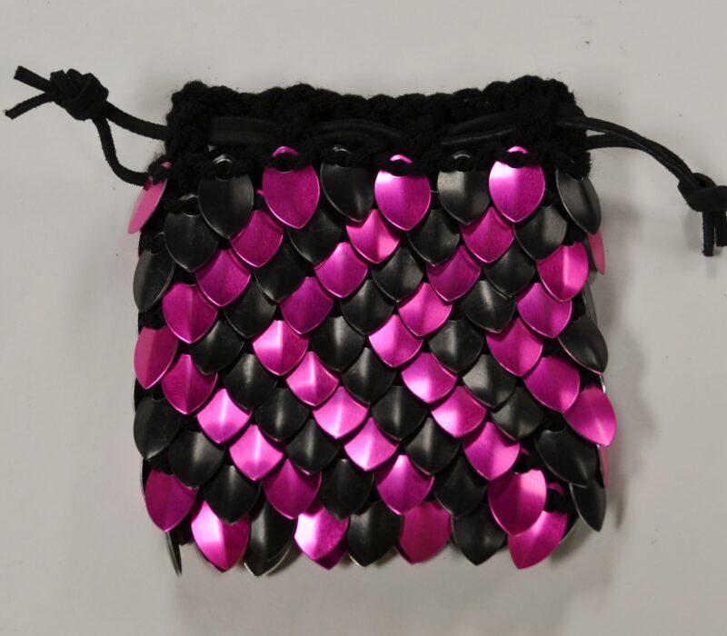 A pink and black zig-zag pattern dragonhide dice bag on black yarn.