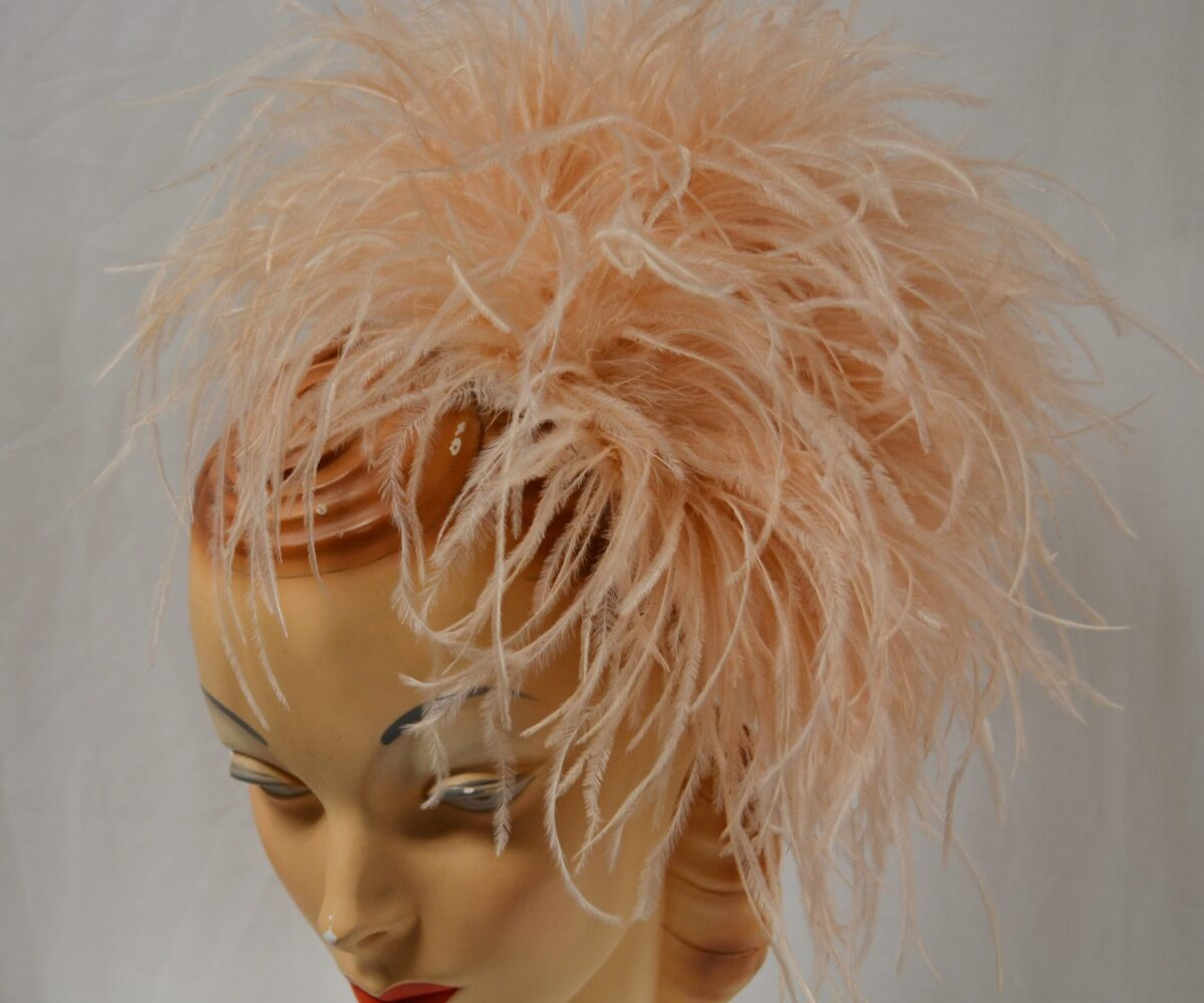A peach-colored feathery fascinator