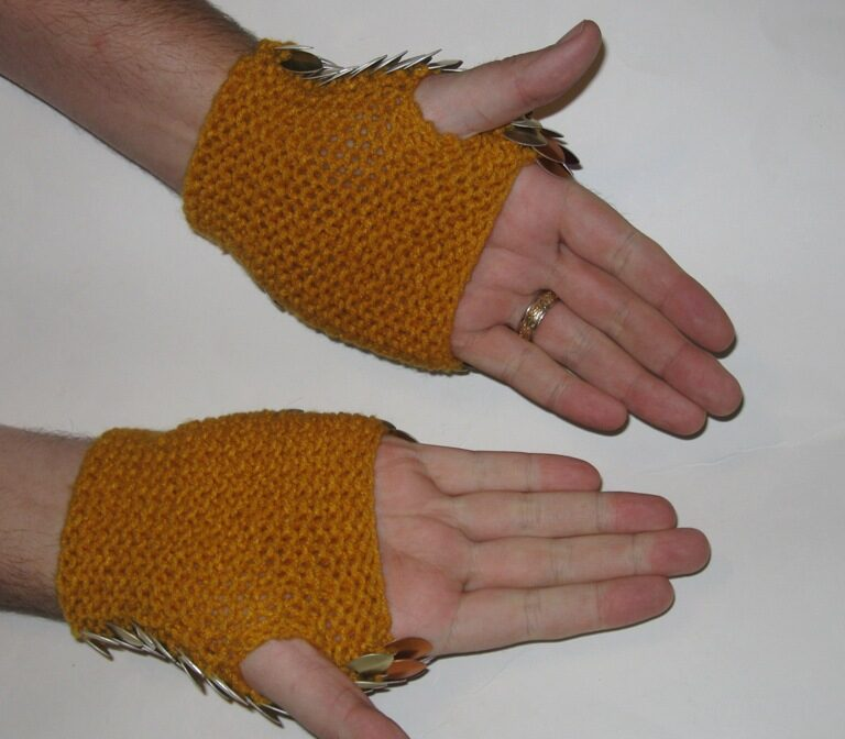 Palm side of a pair of dragonhide gauntlets, showing the soft yellow yarn lining.