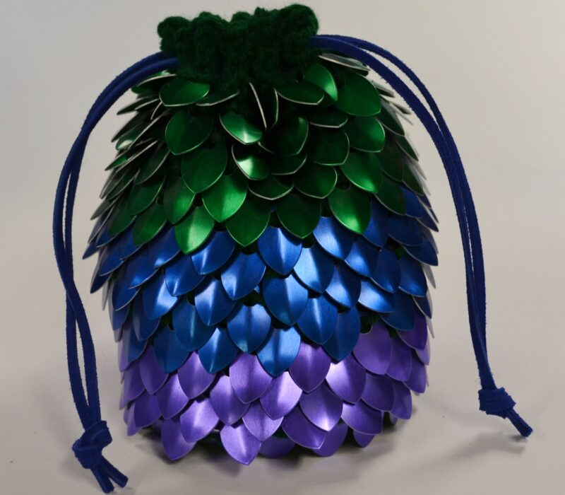 A large dice bag, cinched tight with blue leather drawstrings. The bag is made of knitted scalemaille and has wide green, blue, and purple stripes.