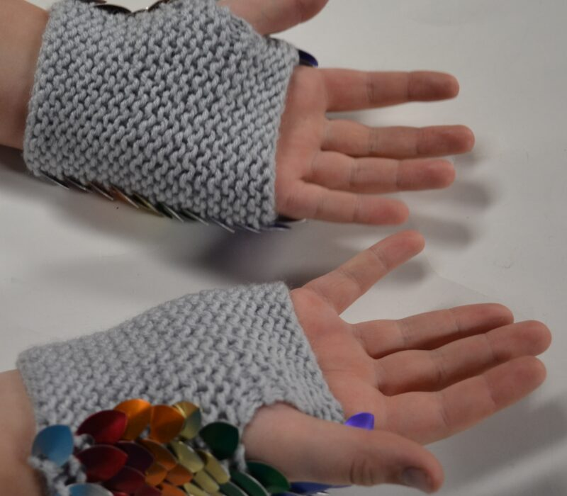 Palm side of a pair of rainbow knitted dragonhide gauntlets, showing the soft grey yarn lining.