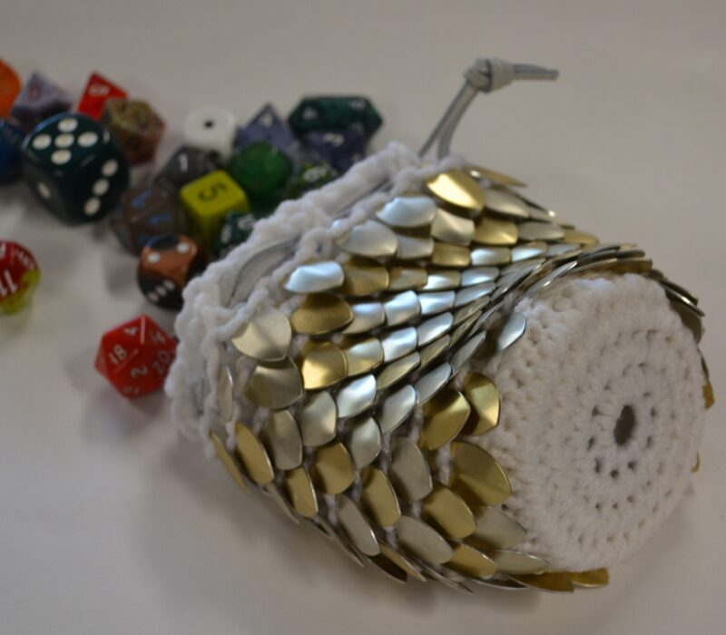A silver and gold scalemaille dicebag on white yarn, spilling dice away from the camera.