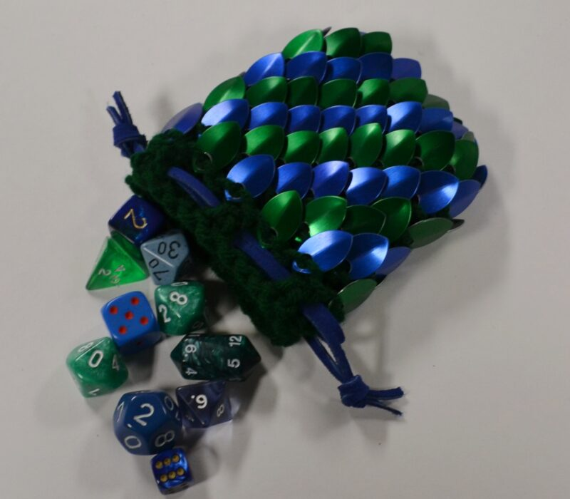 A blue and green scalemaille dicebag, spilling dice onto the table.