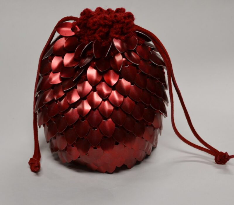 A large red scalemaille dicebag, cinched shut with leather drawstrings.