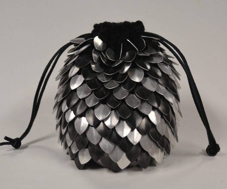 Side view of a silver and black knitted scalemaille dicebag. The top is cinched tight.