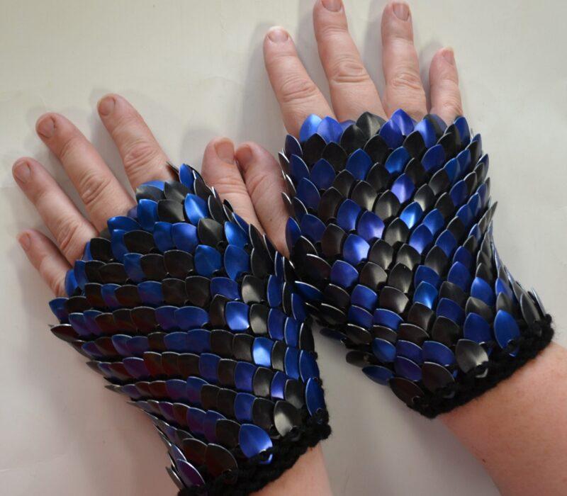 SHort blue and black patterned scalemaille gauntlets on black yarn