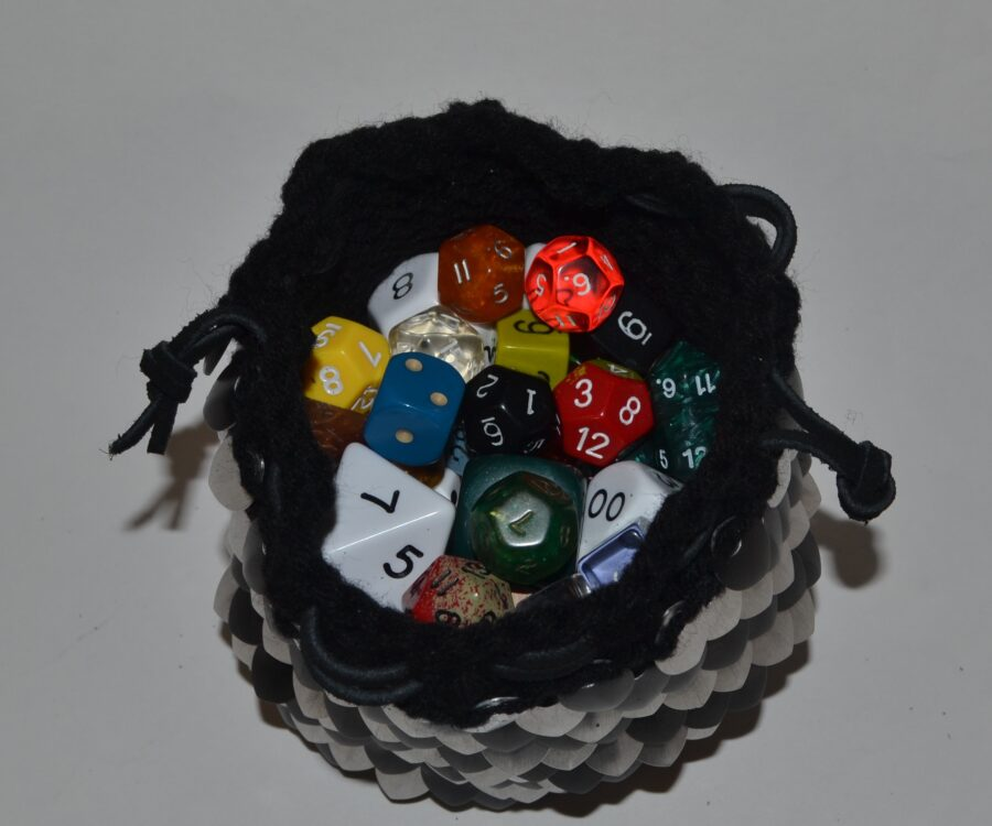 Top view of an open silver and black knitted scalemaille dicebag, full of colorful dice.