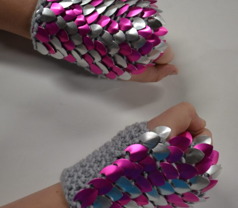 Pink and silver knitted scalemaille gauntlets on grey yarn