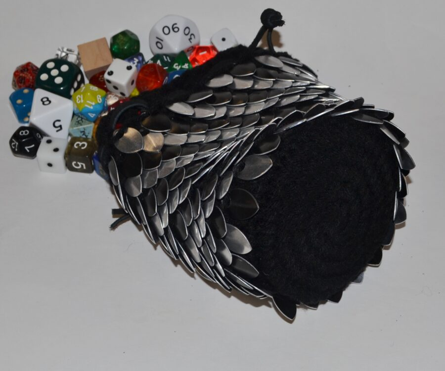 An angled view showing the bottom and side of a silver and black scalemaille dice bag, with dice spilling away from the camera.