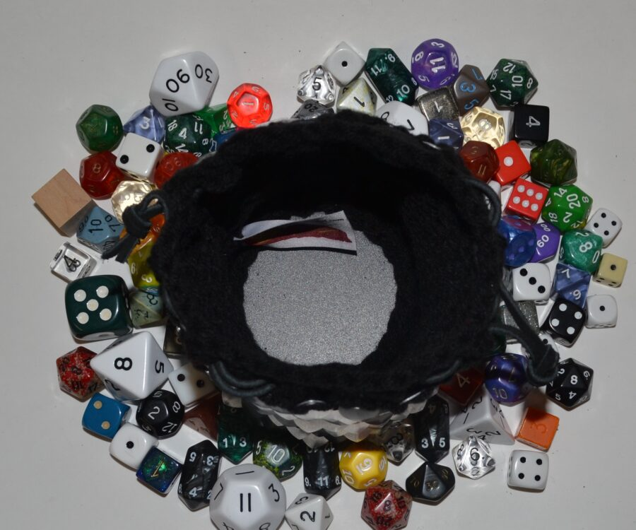 Top view of a silver and black knitted scalemaille dice bag, surrounded by dice. The base is lined with plastic to keep the shape.