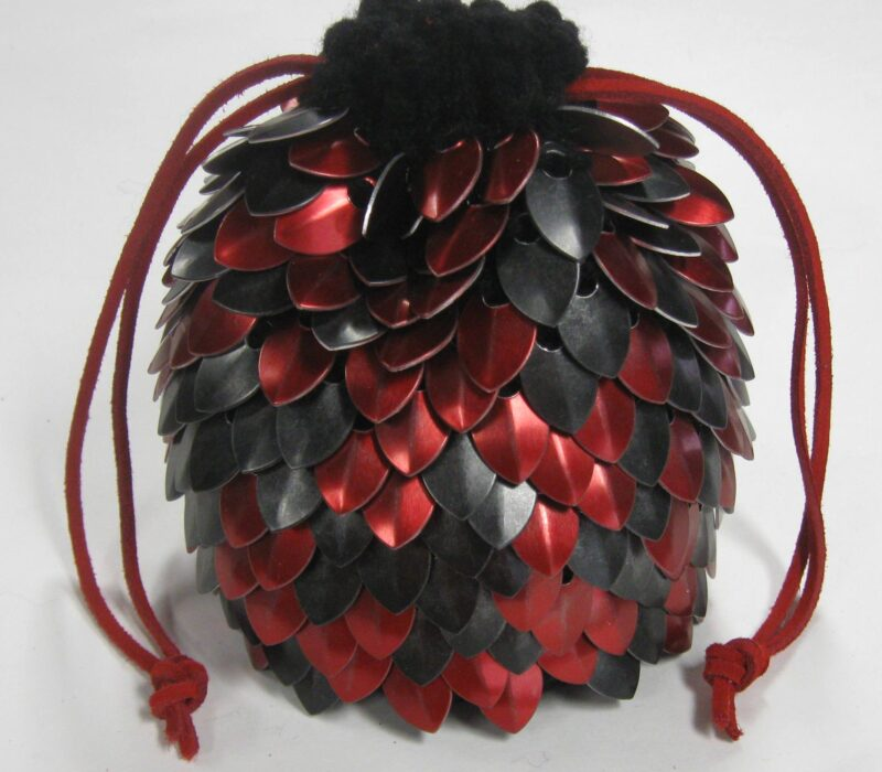 Large red and black scalemaille dicebag with red drawstrings cinching the bag closed.