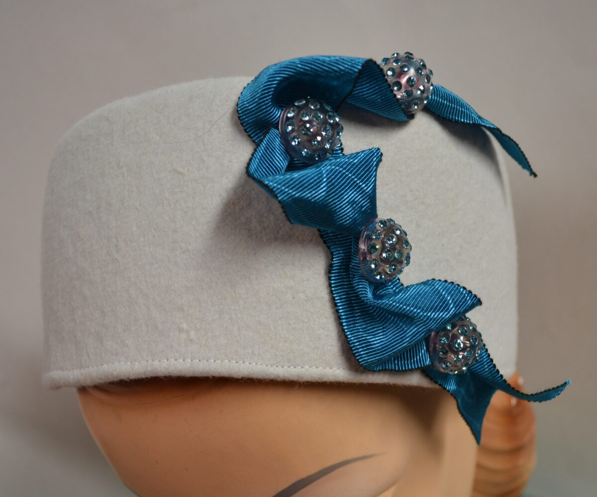 A pale grey pillbox hat with blue ribbon and bejewelled buttons climbing up one side.