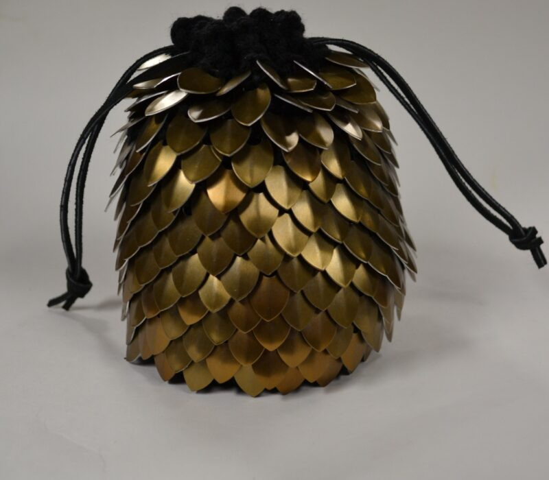 A large gold scalemaille dicebag, cinched shut.