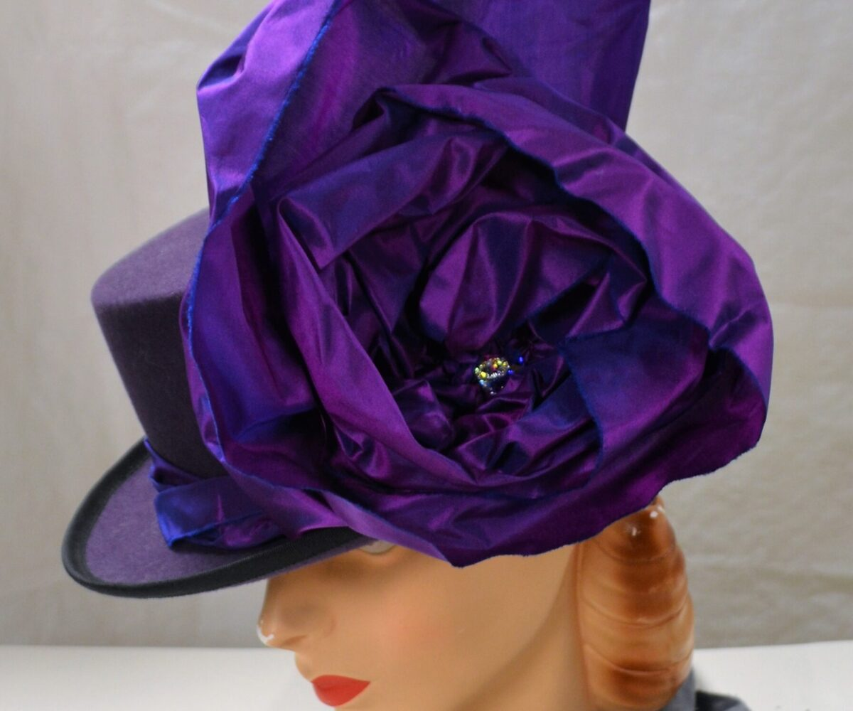 A dark top hat with a large purple flower.