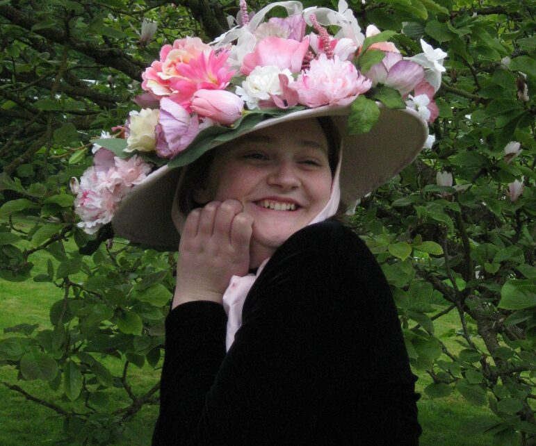 A pink flower-covered hat with a wide brim.