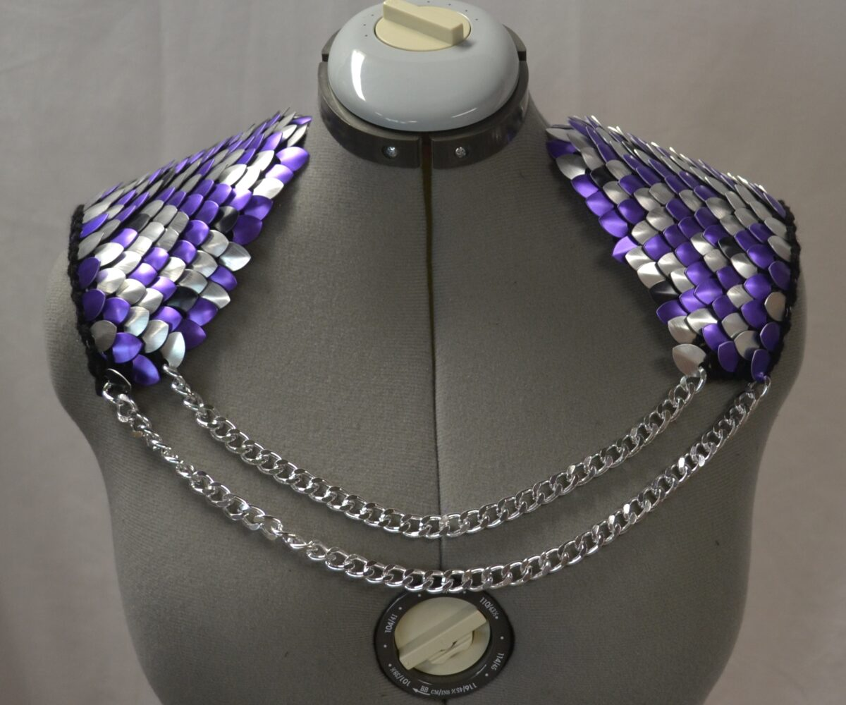 Purple and silver knitted scalemaille epaulets connected by double silver chains, displayed on a dress form.