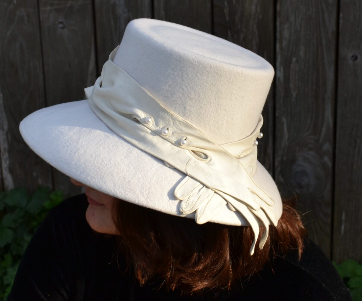 A white felt hat with a wide brim and vintage leather gloves wrapped around it, draping like a ribbon over the brim,