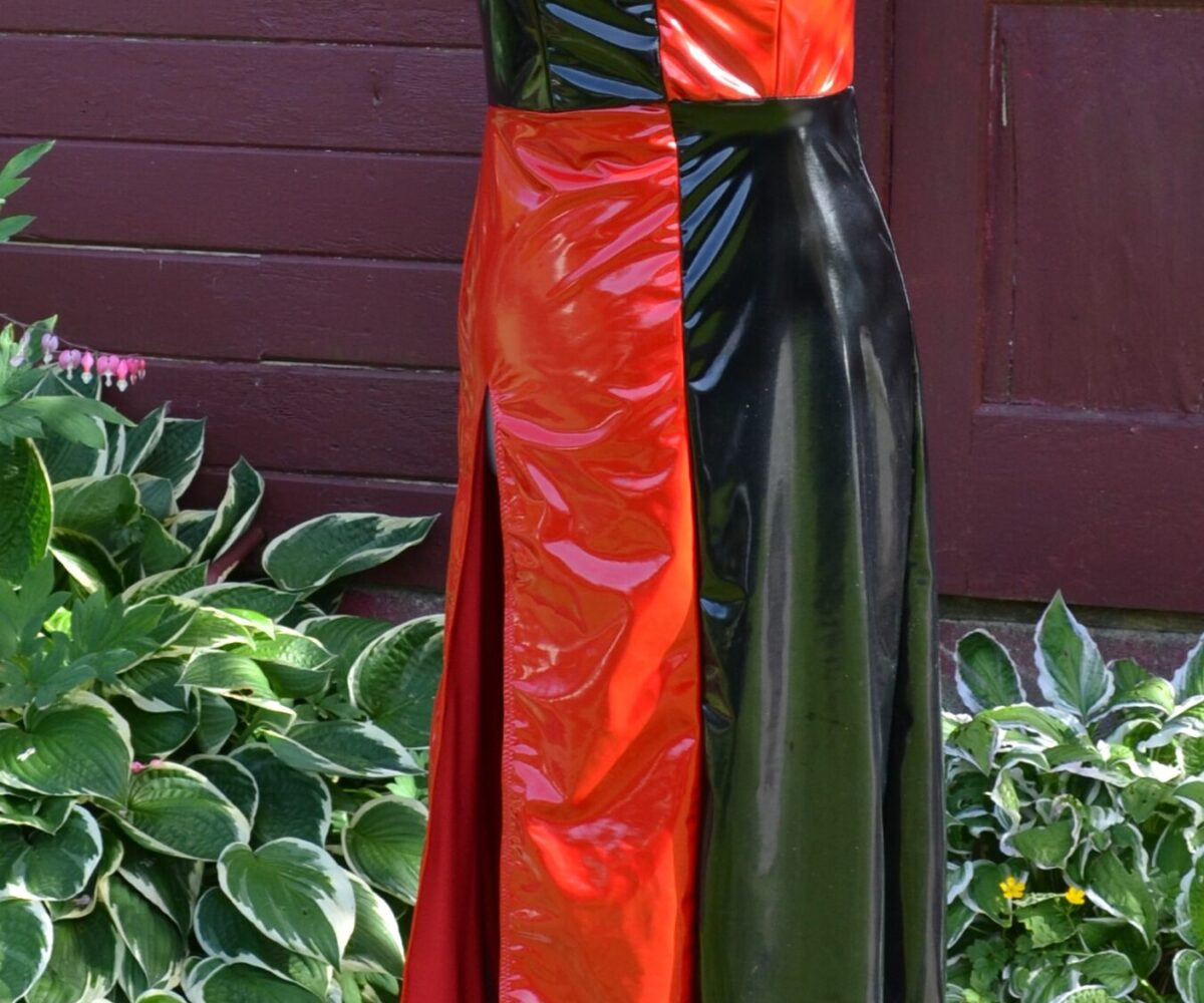 A shiny black and red harlequinn-themed dress, shown on a dress form.