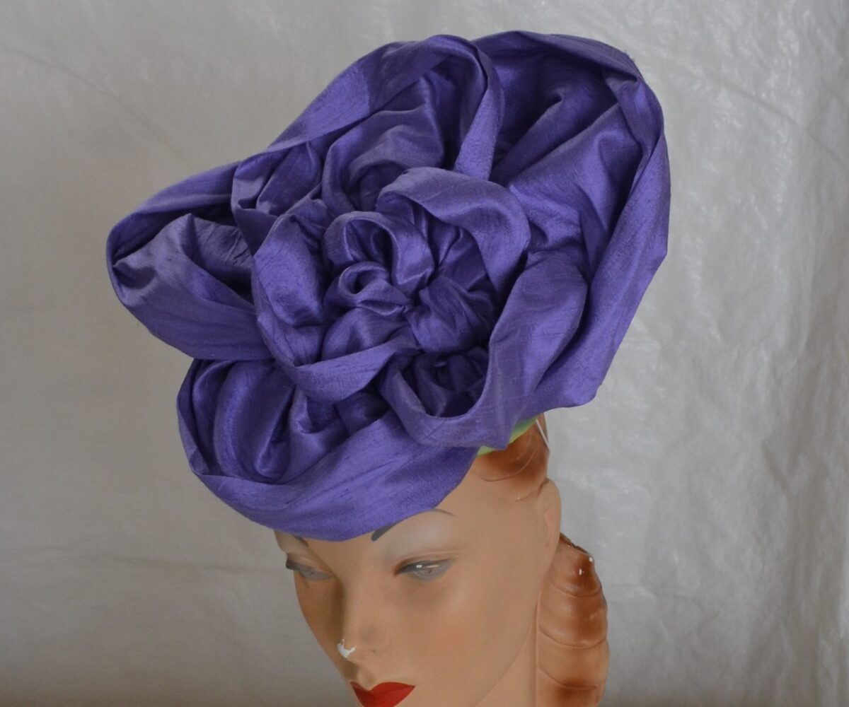 A large purple flower hat, shown from the front