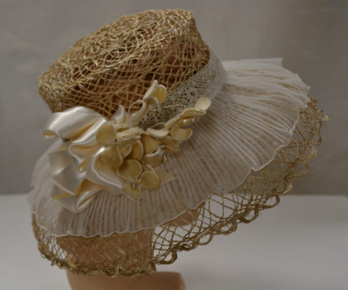 A lacy straw hat with sheer white fabric over the brim, white lace, and cream-colored ribbons and flowers.