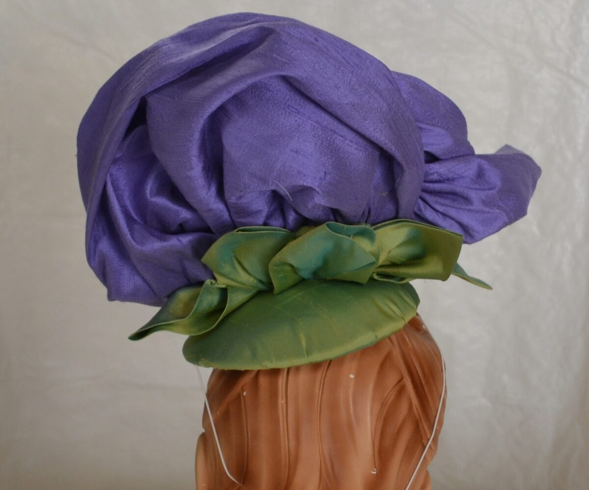 A large purple flower hat with a green leafy base, shown from behind