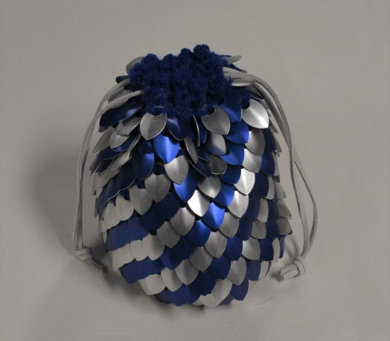 A large, blue and silver striped scalemaille dicebag.