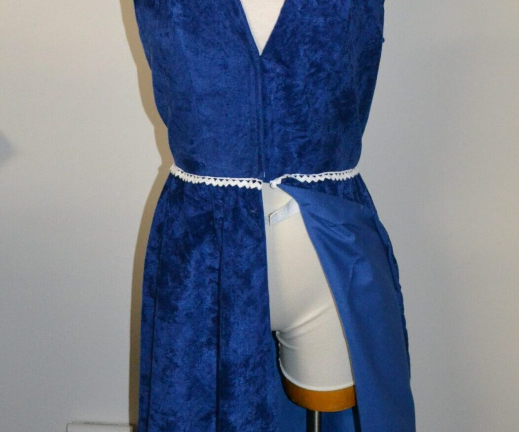 A long blue dress piece with the skirt split down the front, hood up, modelled by a manequinn.
