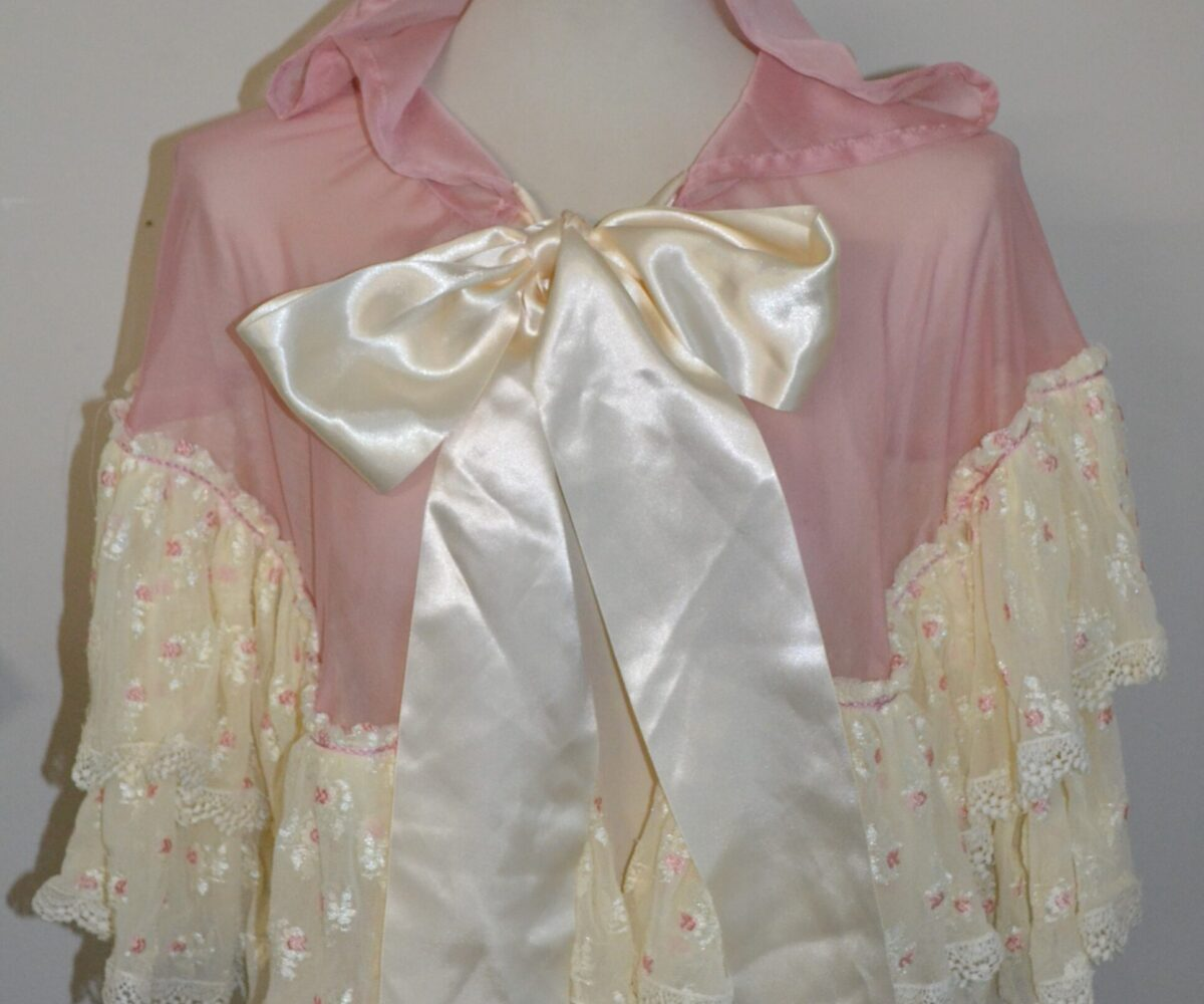 A pink capelet with cream lace around the edges and a wide cream satin ribbon, shown on a mannequin.