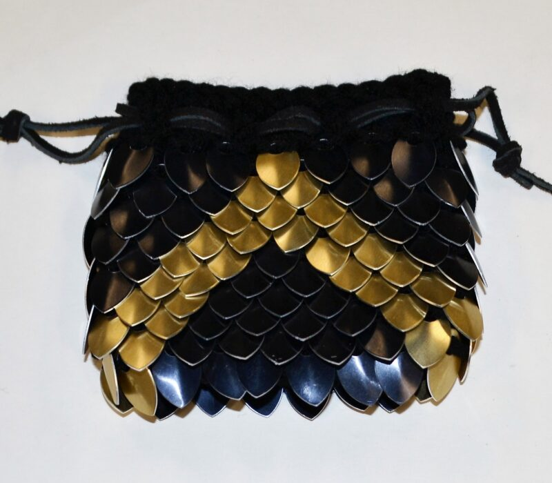 A black scalemaille dicebag with a gold chevron pointing towards the opening.