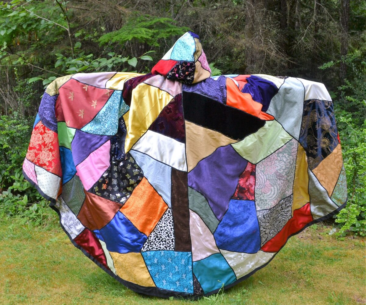 A cloak with large, colorful patchwork panels in a variety of fabrics, shown from the back with the hood up.