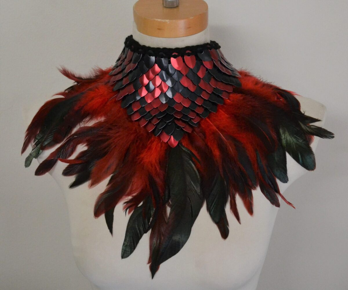A black and red dragonhide collar with matching feather trim, modelled on a mannequin