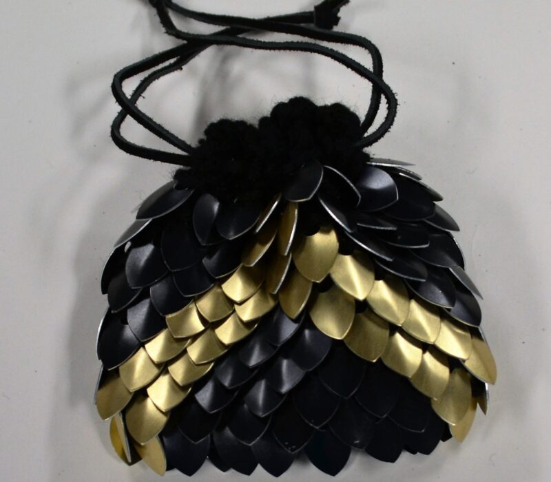 A black scalemaille dicebag with a gold chevron pointing towards the opening, cinched tight with black leather drawstrings.