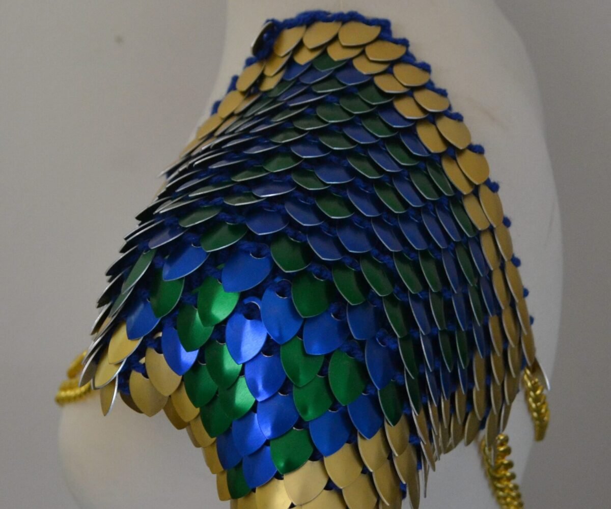 Large knitted scalemaille epaulets in green and blue with a gold border, connected at both shoulders by double gold chains.