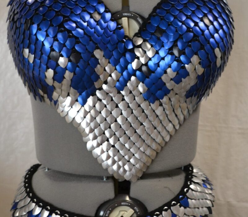 A matching set of blue and silver knitted scalemaille - a bra top in mostly blue, and a loincloth in mostly silver.