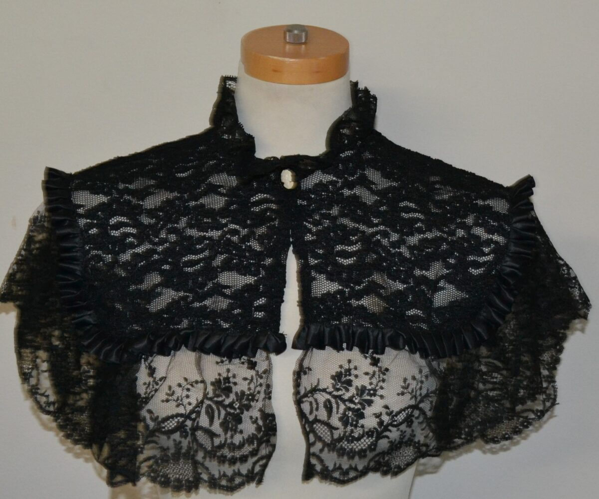 A black lace collar with lighter lace draping around the shoulders, modelled on a manequinn.