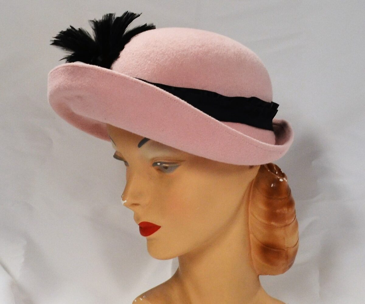 A pink bowler hat with an upturned brim and black ribbon. A spray of black feathers is peaking up from the other side of the hat.
