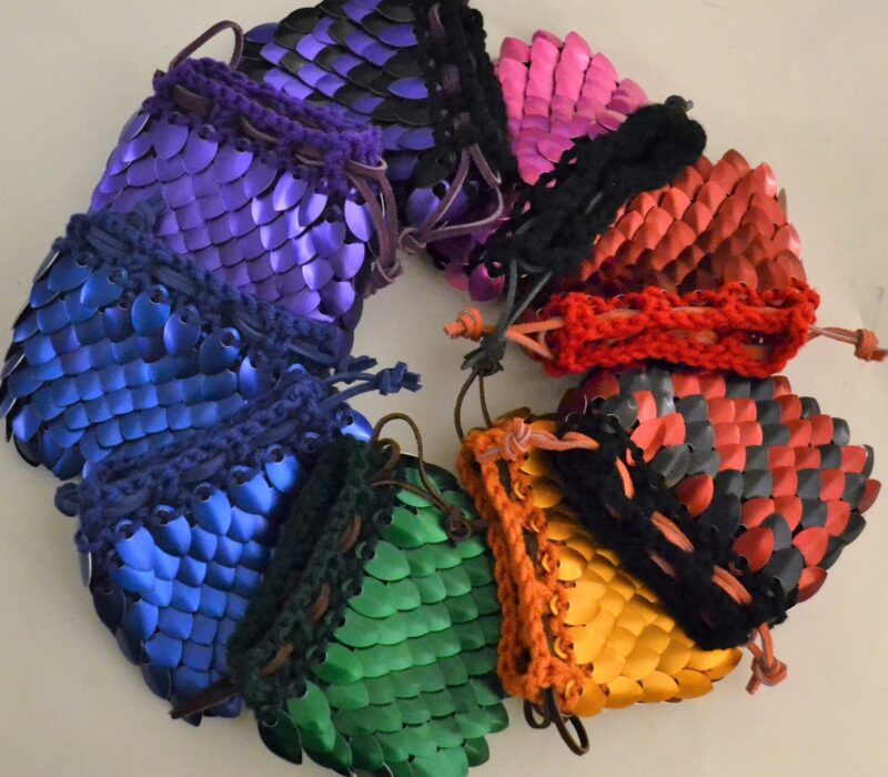 A variety of colorful medium knitted scalemaille dicebags, arranged in a circle.