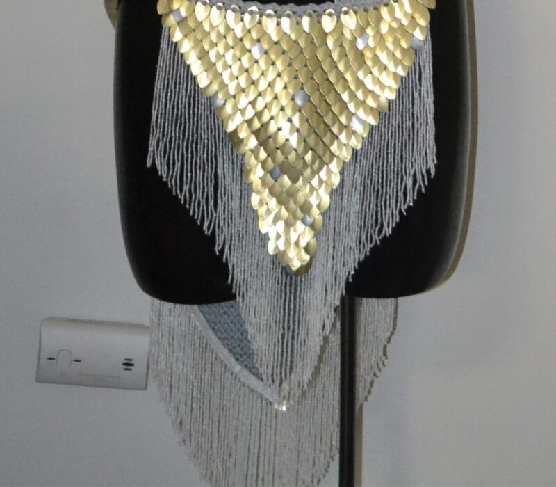 A matching set of knitted dragonhide in gold - a collar with gold trim, and a loincloth with white trim.