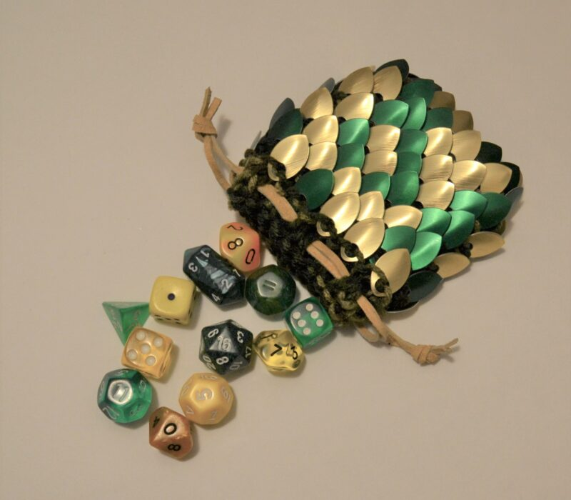 A medium gold and green scalemaille dice bag, open and spilling dice out.
