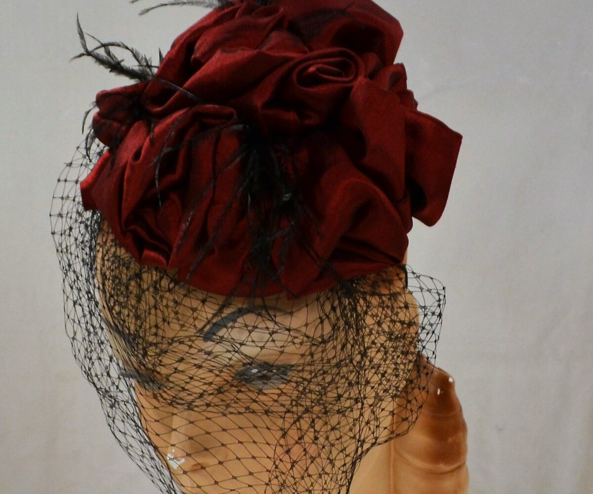 A red rose-like fascinator with a black veil and thin black feathers.