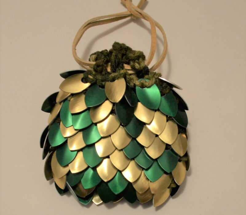 A medium gold and green scalemaille dice bag, cinched tight with tan leather straps.
