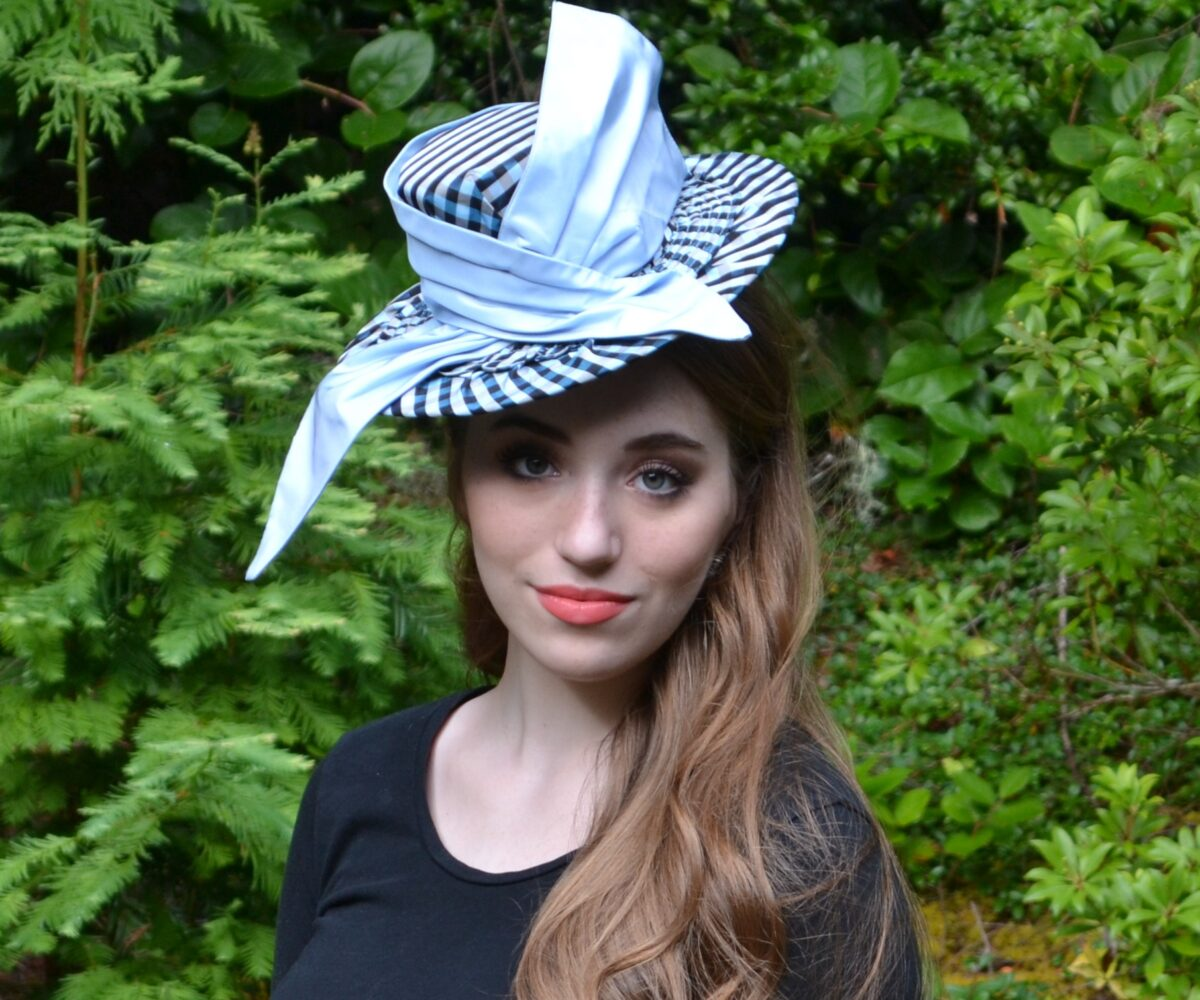 A gingham-patterned hat with lighter, solid ribbon, modelled by a youngh woman.