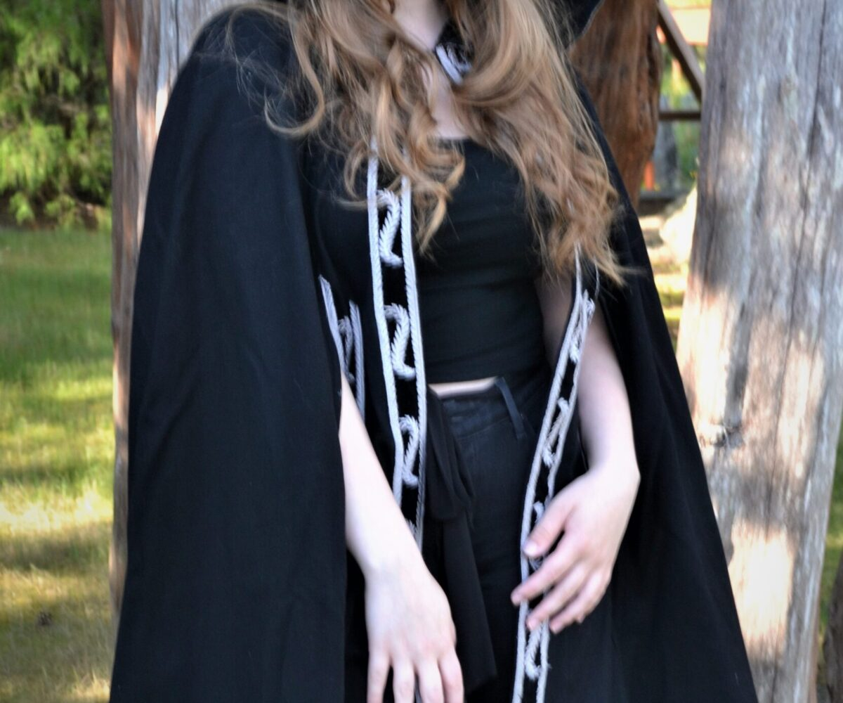 A knee-length black cape with white patterned trim, modelled by a young woman.