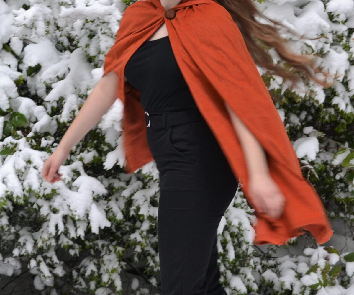 An orange thigh-length cape, modelled by a young woman spinning in the snow.