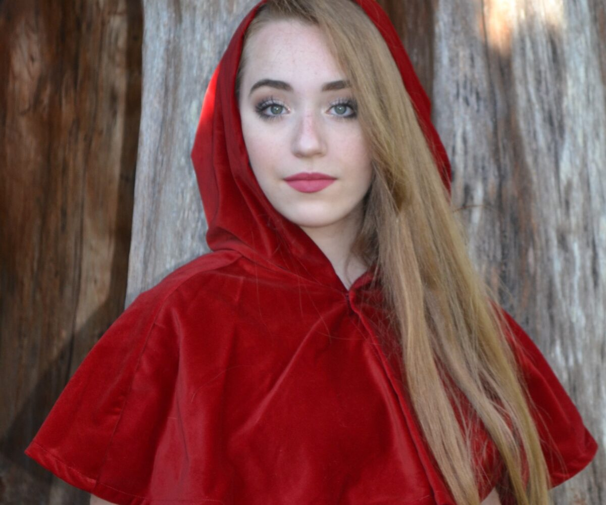 A red capelet, the hood up, modelled by a young woman.